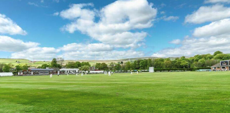 image of the littleborough cricket ground with blue sky and white fluffy clouds